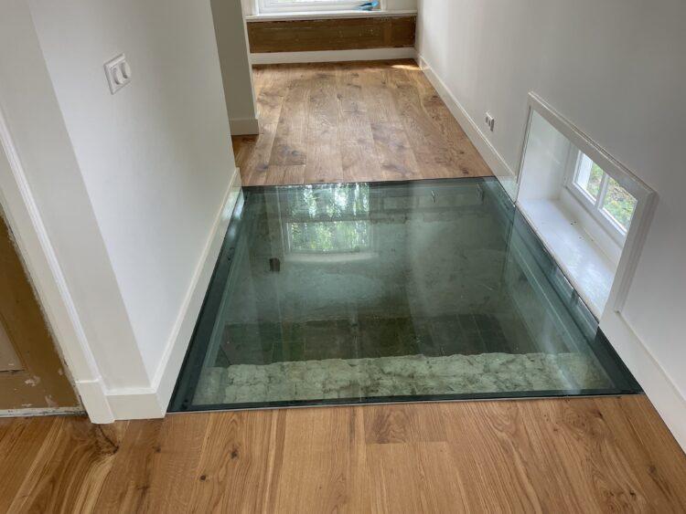 De nieuwe doorgang met de glasplaat boven de kelder