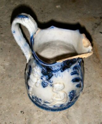 Stenen kan , blauw/wit met barokke afbeelding (scherven zijn eraf)