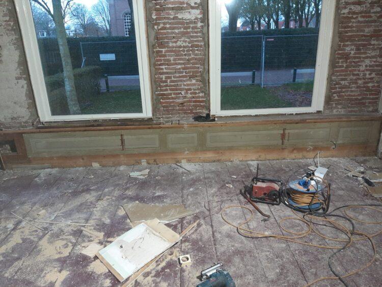 De houten panelen onder de kozijnen aan de westzijde worden na het isoleren van de wanden weer terug geplaatst.