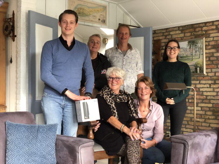 Lina Kool ontvangt de gedigitaliseerde films uit handen van Jurjen Enzing (links, FFA).  Verder op de foto staand naast Jurjen van links naar rechts: Carla Duim (Historisch Centrum Leeuwarden), Syds Wiersma (FFA) en Kelly Bauer (FFA). Zittend van links naar rechts: Lina Kool en Joyce van Bon ('t Heer en Feer).