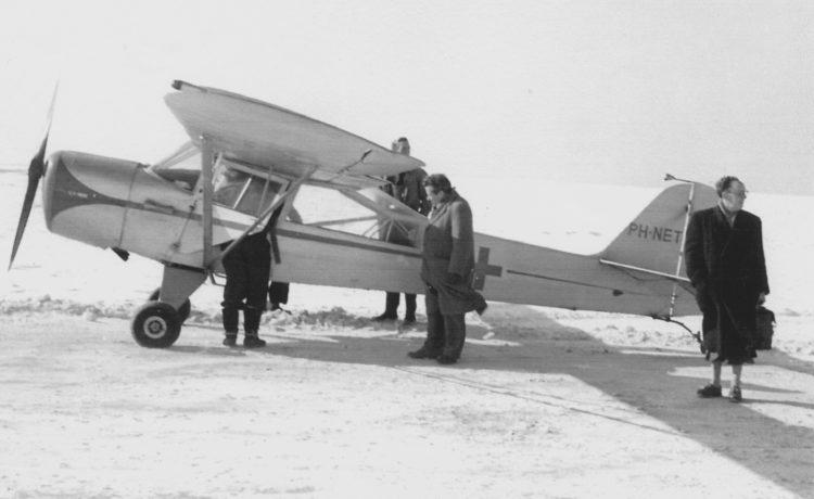 Het eigen Waddenvliegtuig wit geschilderd en uitgerust met brancard en een rood kruis op de romp (winter 1956). Foto: Jan Holwerda.