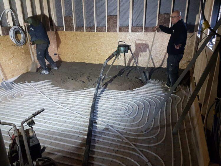 De vloerverwarming is aangebracht, de cementdekvloer wordt gestort